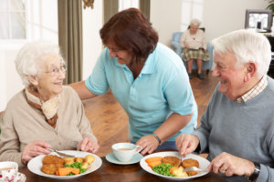 caregiver preparing meal for the senior patients